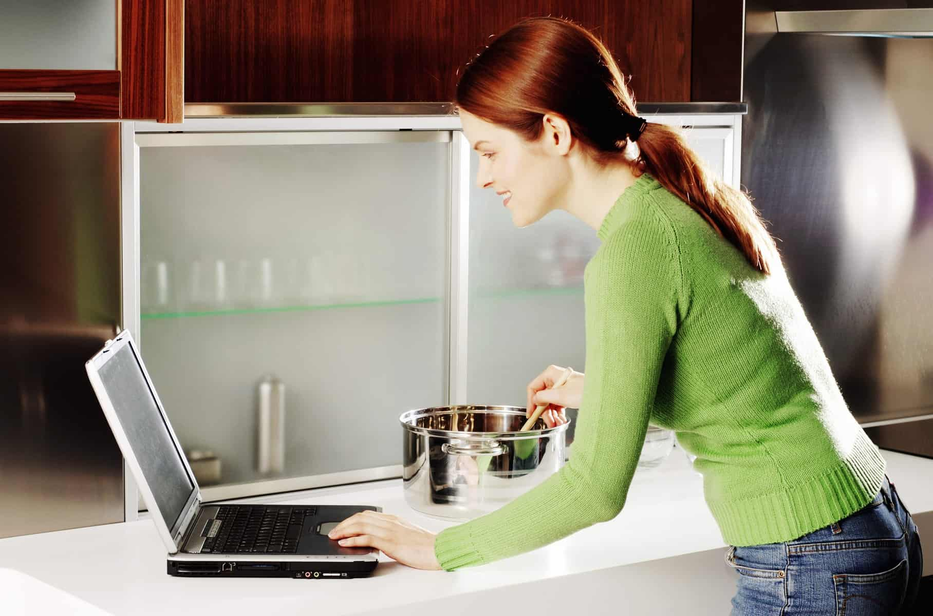 online jobs for homemakers - Woman using laptop while cooking in the kitchen