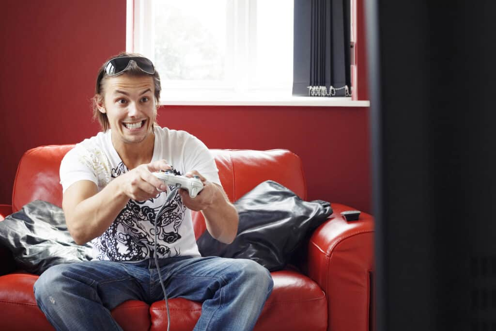 man sitting on the couch ready to earn money playing games