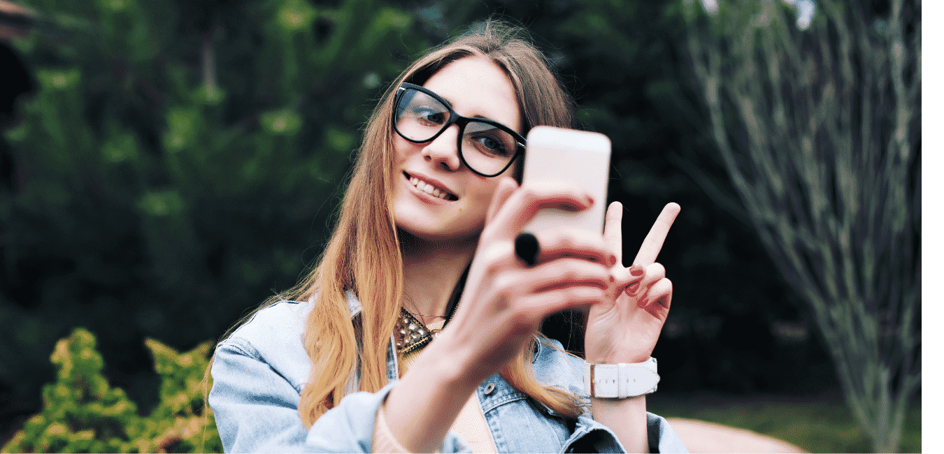Woman taking a selfie. How to get paid for photos of yourself